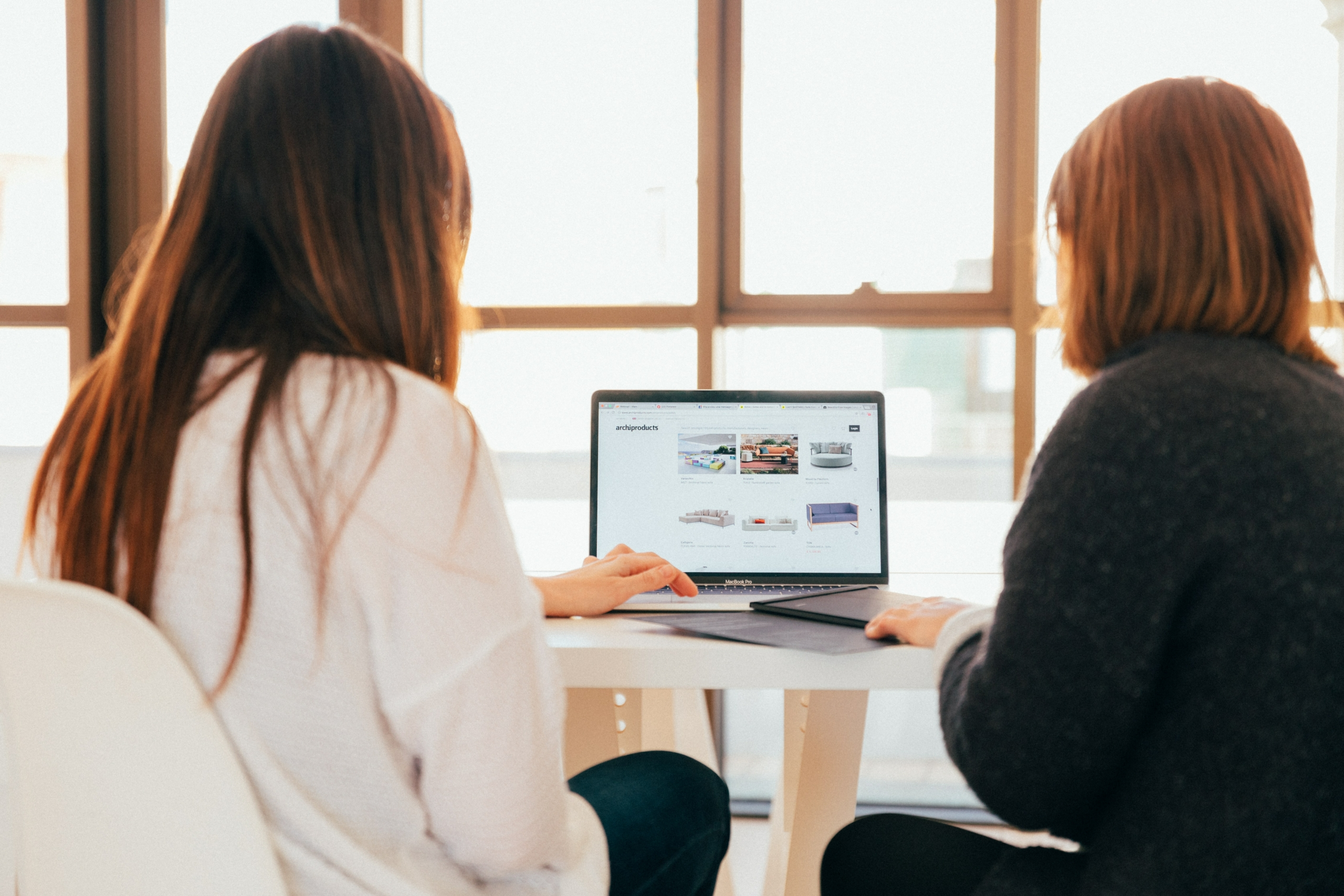 Women looking over computer data to enhance the customer experience